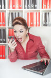 Angry screaming business woman with telephone. In office Royalty Free Stock Photography