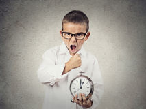 Angry screaming, child, boy holding alarm clock. Closeup portrait, Angry, Mad, pissed off Child, Boy, playing boss manager, Screaming, about to smash alarm clock Royalty Free Stock Image