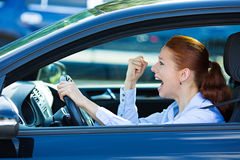Angry, screaming female car driver. Closeup portrait displeased angry pissed off aggressive woman driving car, shouting at someone, fist hand up in air isolated Stock Image
