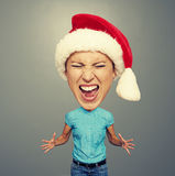 Angry screaming girl in santa hat. Over grey background Stock Photo