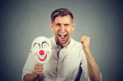 Angry screaming man holding clown mask expressing cheerfulness happiness. Portrait young upset angry screaming man holding a clown mask expressing cheerfulness royalty free stock photography