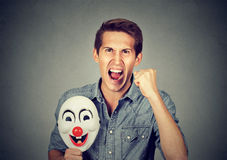 Angry screaming man holding clown mask expressing cheerfulness. Portrait young upset angry screaming man holding a clown mask expressing cheerfulness happiness stock photography