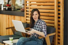 Angry screaming sad upset girl in outdoors street coffee shop wooden cafe sitting with modern laptop pc computer. Disturb problem during free time. Mobile royalty free stock photography
