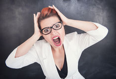 Angry screaming teacher on blackboard background. Angry screaming teacher on chalkboard blackboard background stock photo