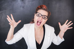 Angry screaming teacher on blackboard background. Angry screaming teacher on chalkboard blackboard background stock photography