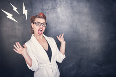 Angry screaming teacher on chalkboard background. Angry screaming teacher on chalkboard blackboard background royalty free stock images