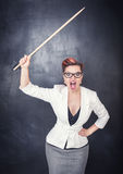 Angry screaming teacher with pointer on blackboard background. Angry screaming teacher with pointer on the chalkboard blackboard background stock photo