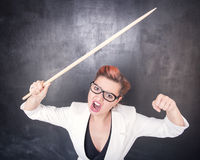 Angry screaming teacher with pointer on blackboard background Stock Photography