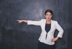 Angry screaming teacher pointing out on blackboard. Background royalty free stock photo