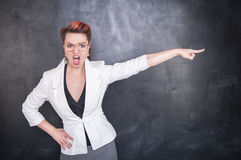 Angry screaming teacher pointing out blackboard background. Angry screaming teacher pointing out on chalkboard blackboard background Stock Photos