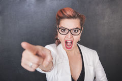 Angry screaming teacher pointing out on chalkboard background. Angry screaming teacher pointing out on chalkboard blackboard background stock images