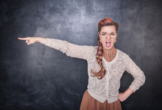 Angry screaming teacher pointing out. On chalkboard blackboard background royalty free stock images