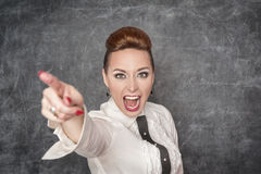 Angry screaming teacher pointing out. Angry screaming teacher in white blouse pointing out royalty free stock photo