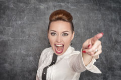 Angry screaming teacher pointing out. Angry screaming teacher in white blouse pointing out stock photography