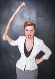 Angry screaming teacher with wooden stick on blackboard backgrou Royalty Free Stock Photography