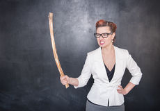 Angry screaming teacher with wooden stick on blackboard background. Angry screaming teacher with wooden stick on chalkboard blackboard background royalty free stock photo