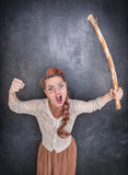 Angry screaming teacher with wooden stick. On chalkboard blackboard background royalty free stock photos