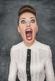 Angry screaming woman. On the blackboard background stock image