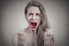 Angry screaming woman hysterical having breakdown. Screaming girl. Closeup portrait angry young woman hysterical having nervous breakdown fists up in air Royalty Free Stock Image