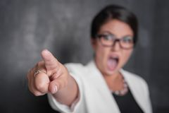 Angry screaming woman pointing out. Focus on hand. Angry screaming woman pointing out on blackboard background. Focus on hand royalty free stock image
