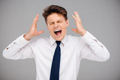 Angry screaming young man. Irritated young man screaming. Concept for office problems and stress Stock Images