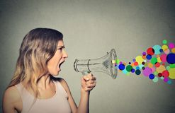 Angry screaming young woman holding megaphone. Portrait angry screaming young woman holding megaphone isolated on grey wall background. Negative face expression Royalty Free Stock Photo