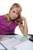 Angry secretary. Working at her desk Stock Photo