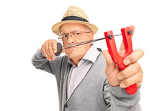 Angry senior aiming to shoot a rock with a slingshot Royalty Free Stock Image