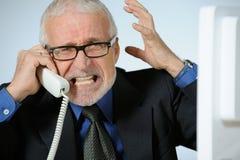 Angry senior businessman. Horizontal image of angry senior businessman calling Royalty Free Stock Images
