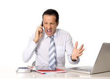 Angry senior businessman in stress working and talking on mobile phone angry Stock Photo