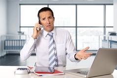 Angry senior businessman in stress working and talking on mobile phone at computer desk Stock Photos