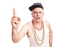 Angry senior with a hip-hop cap and a golden chain. Around his neck threatening with his finger isolated on white background Royalty Free Stock Photography