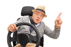 Angry senior holding a steering wheel and cursing stock images
