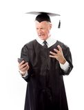 Angry senior male graduate screaming on a mobile phone Royalty Free Stock Photos