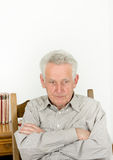 Angry senior man. Angry old man with crossed arms looking under the brows Royalty Free Stock Photo