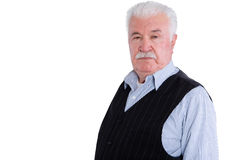 Angry senior man with mustache over white. Firm and angry senior man wearing vest with intimidating and serious expression over isolated background Stock Images