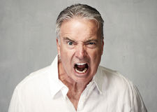 Angry senior man. Angry screaming senior man over gray wall background stock photo