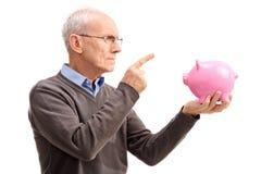 Angry senior scolding a piggybank Stock Photo