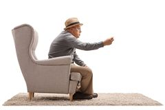 Angry senior sitting in an armchair and arguing Royalty Free Stock Image