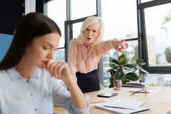 Angry senior woman shouting at her employee. Go away. Angry unhappy senior women looking at her employee and shouting at her while pointing at the door Stock Image