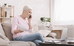 Upset senior woman talking on phone and working at home. Angry senior woman talking on phone and working at home, looking at laptop and waving paper royalty free stock image
