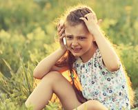 Angry serious cute kid girl sitting on the glass, talking on mob. Ile phone and scratching the head on summer green grass background. Toned closeup fun portrait Royalty Free Stock Photography