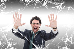 Angry and shocked businessman holding broken glass wall Royalty Free Stock Image