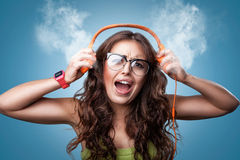 Angry shocked girl in headphones listening to music. Royalty Free Stock Image