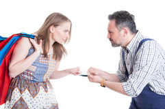 Angry shopaholic and mechanic man arguing for debit card royalty free stock image