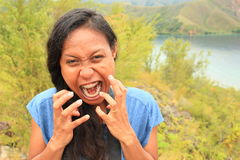Angry shouting girl. Angry shouting tropical girl - portrait of crazy young Papuan woman with bay on sea behind - Papua Barat, Indonesia Royalty Free Stock Image