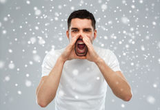 Angry shouting man in t-shirt over snow background. Emotions, communication, winter, christmas and people concept - angry shouting man in t-shirt over snow on Stock Photography