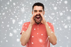 Angry shouting man in t-shirt over snow background. Emotions, communication, winter, christmas and people concept - angry shouting man in t-shirt over snow on Royalty Free Stock Images
