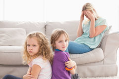 Angry siblings sitting arms crossed with sad mother on sofa Royalty Free Stock Photo