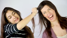 Angry sisters pulling long hair screaming fighting Royalty Free Stock Photos